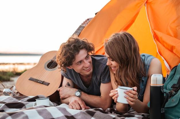 Gelukkige jonge paar liegen en het drinken van thee in toeristische tent op het strand