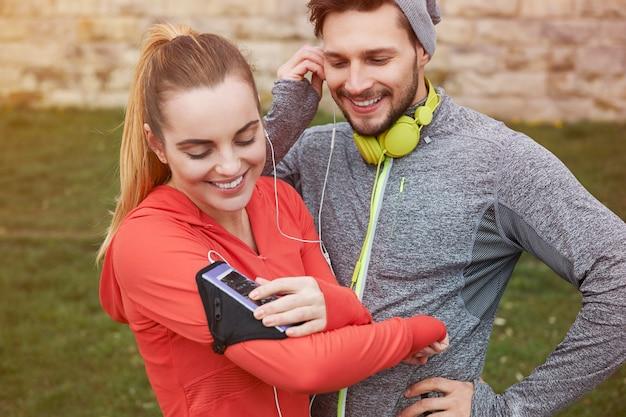 Gelukkige jonge paar luisteren muziek met oortelefoons