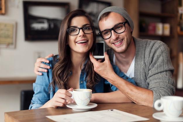 Gelukkige jonge paar luisteren stem van mobiele telefoon