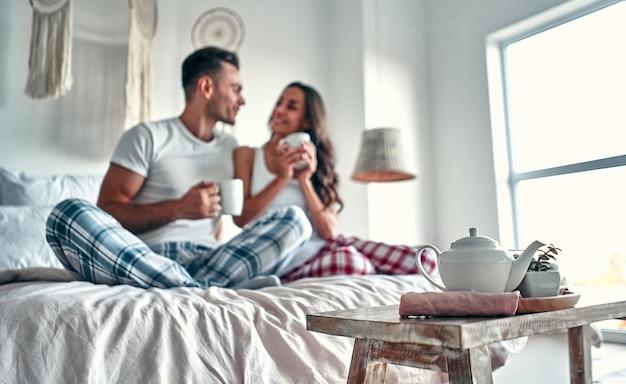 Gelukkige jonge paar praten en lachen zittend op het bed en thuis koffie drinken in de ochtend.