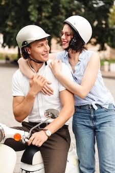 Gelukkige jonge paar samen op motor in de stad straat, lachen