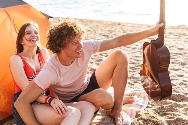 Gelukkige jonge paar samen zitten op het strand, kamperen, gitaar spelen