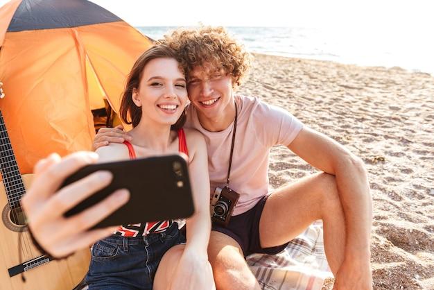 Gelukkige jonge paar samen zitten op het strand, kamperen, selfie te nemen
