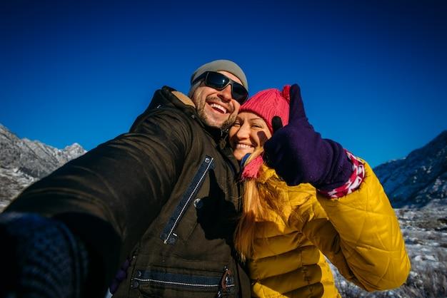 Gelukkige jonge paar selfie te nemen tijdens de wintervakantie in de bergen