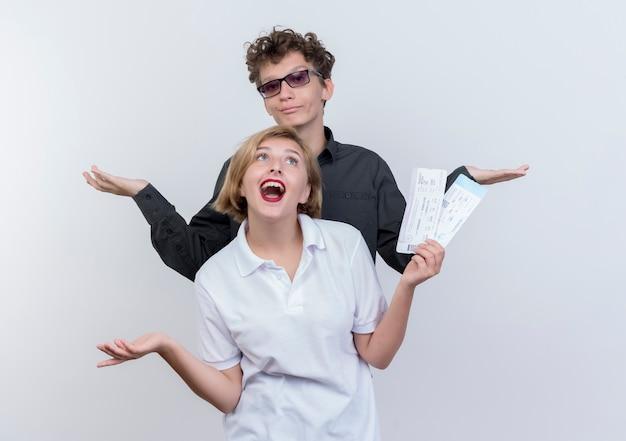 Gelukkige jonge paar toeristenman en vrouw met vliegtickets die pret hebben die samen over witte muur staan
