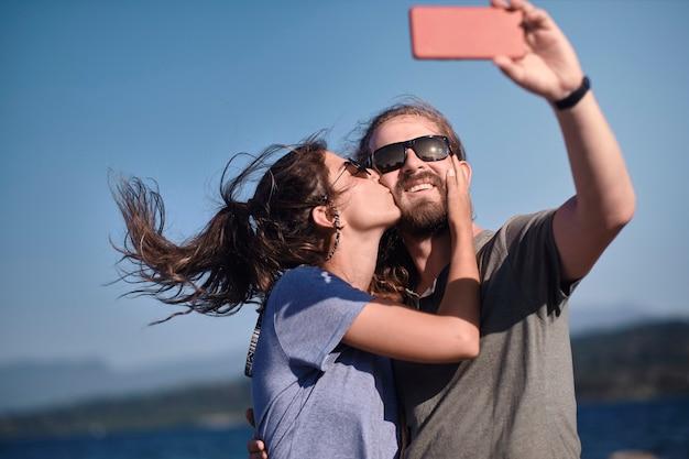 Gelukkige jonge paar verliefd met plezier en het nemen van een portret selfie op het strand.