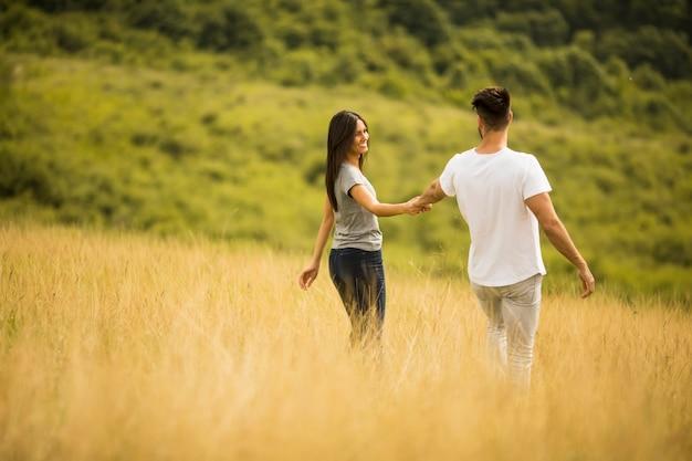 Gelukkige jonge paar verliefd wandelen door grasveld