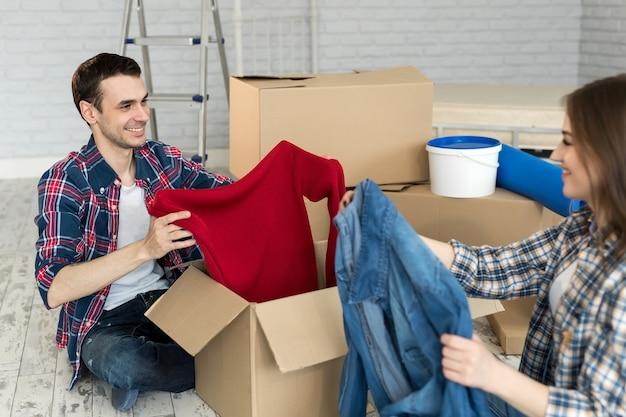 Gelukkige jonge paar verplaatsen in nieuw huis dozen uitpakken, plezier