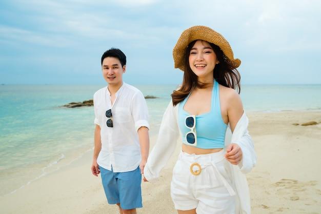 Gelukkige jonge paar wandelen op het strand van koh munnork island, rayong, thailand