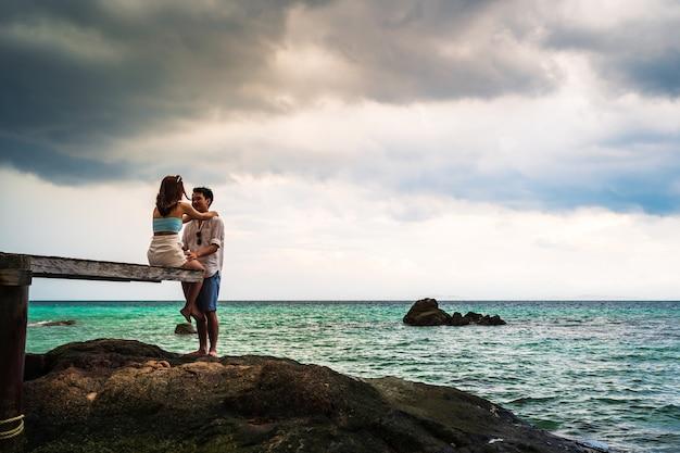 Gelukkige jonge paar zittend op een houten brug en zee strand op koh munnork island, rayong, thailand