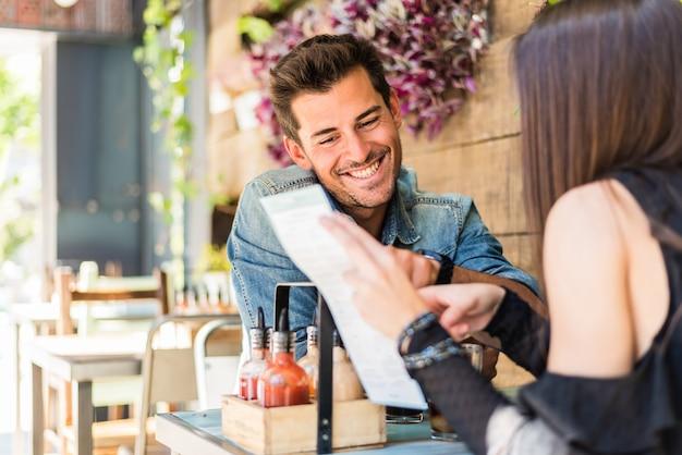 Gelukkige jonge paarplaatsing in een restaurant die het menu bekijken
