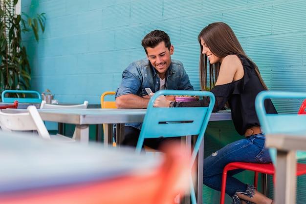 Gelukkige jonge paarplaatsing in een restaurant met een smartphone