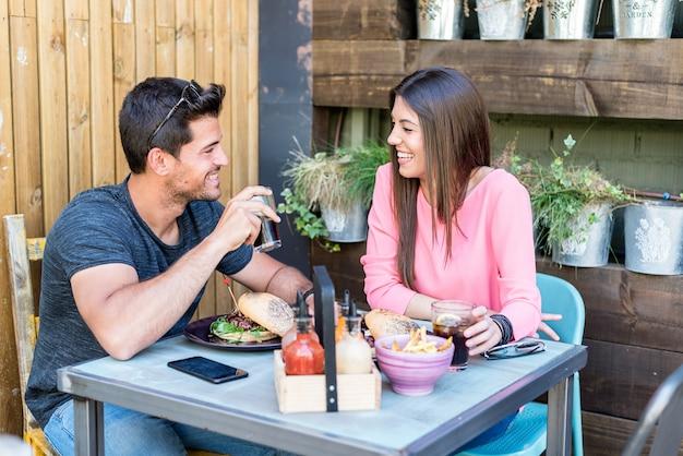 Gelukkige jonge paarplaatsing in een restaurantterras die een hamburger eten