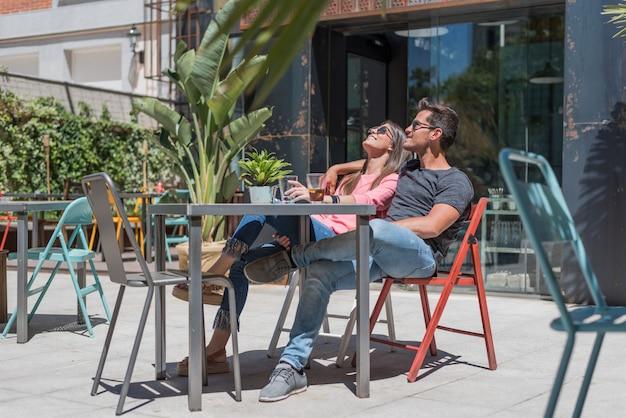 Gelukkige jonge paarplaatsing ontspannen in een restaurantterras