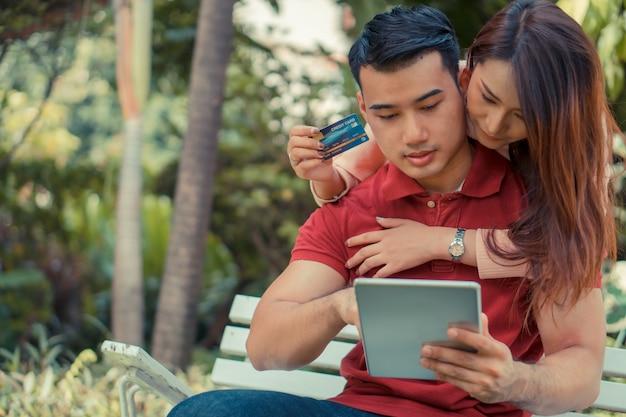 Gelukkige jonge paarzitting in de tuin en holding een tablet en een creditcard die momenteel producten kopen