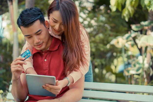 Gelukkige jonge paarzitting in de tuin en holding een tablet en een creditcard