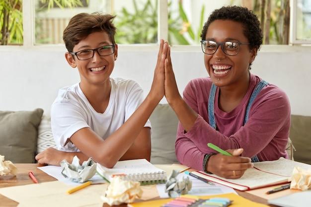 Gelukkige jonge partners werken samen in de werkruimte, geven elkaar high five, hebben uitgelaten uitdrukkingen, werken aan onderzoek, noteren records in notitieblok, denken na over een idee, werken als team.