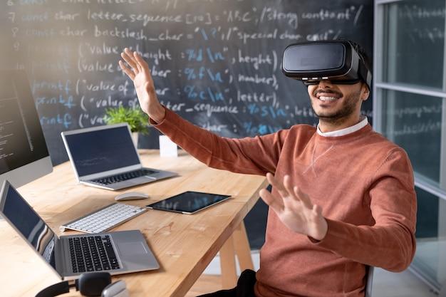 Gelukkige jonge programmeur die vr-bril draagt bij bureau met laptops en virtuele vertoning bekijkt