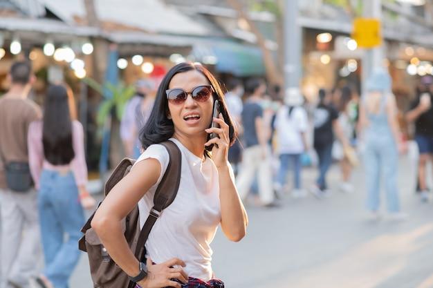 Gelukkige jonge reis aziatische vrouw die mobiele telefoon op een straatmarkt met behulp van.