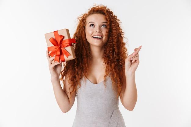 Gelukkige jonge roodharige krullende vrouw met een verrassingsdoosje maakt een hoopvol gebaar.