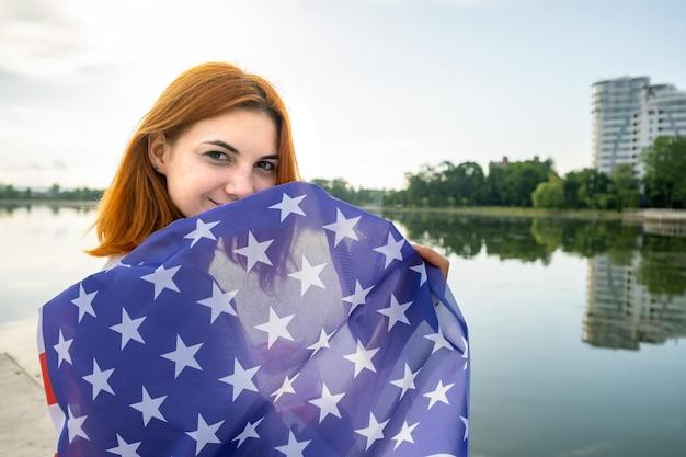 Gelukkige jonge roodharige vrouw met de nationale vlag van de vs op haar schouders die zich buiten bevinden