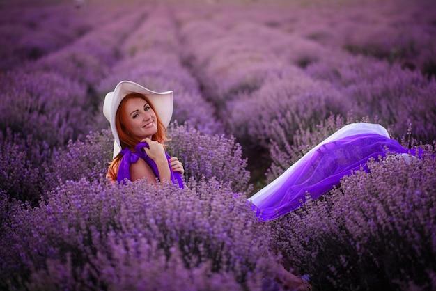 Gelukkige jonge roodharige vrouwenzitting in lavendelgebied bij zonsondergang