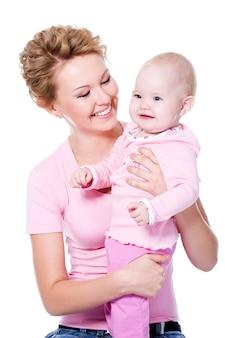 Gelukkige jonge schoonheidsmoeder die met aantrekkelijke glimlach haar baby houdt - die op wit wordt geïsoleerd