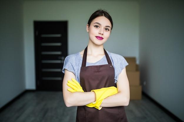 Gelukkige jonge schoonmaakster die rubberen handschoenen aantrekt en zich klaarmaakt voor de lenteschoonmaak