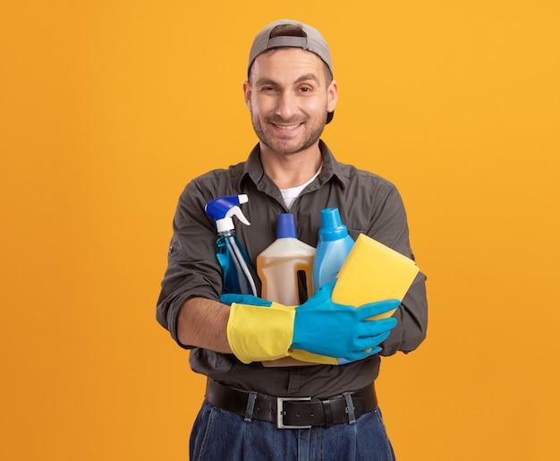 Gelukkige jonge schoonmakende mens die vrijetijdskleding en glb in rubberhandschoenen draagt die nevelfles en spons houden die vrolijk over oranje muur glimlacht