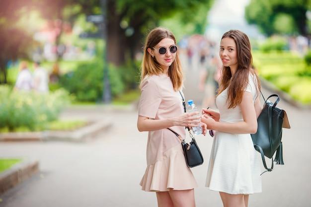 Gelukkige jonge stedelijke meisjes in europese stad. blanke vrouwen plezier samen en genieten van hun weekend buiten