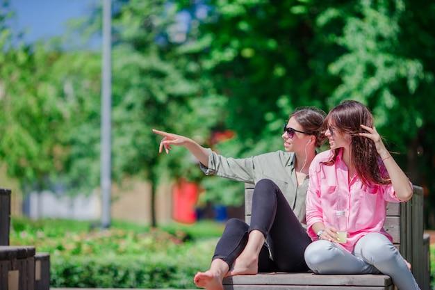 Gelukkige jonge stedelijke meisjes in europese stad. kaukasische mooie vrouwen plezier samen buitenshuis