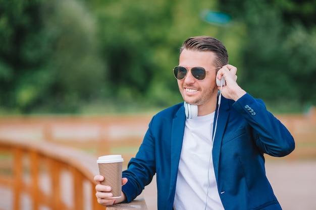 Gelukkige jonge stedelijke mens die en koffie in europese stad in openlucht werken drinken