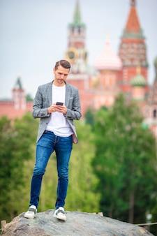 Gelukkige jonge stedelijke mens het drinken koffie in europese stad.