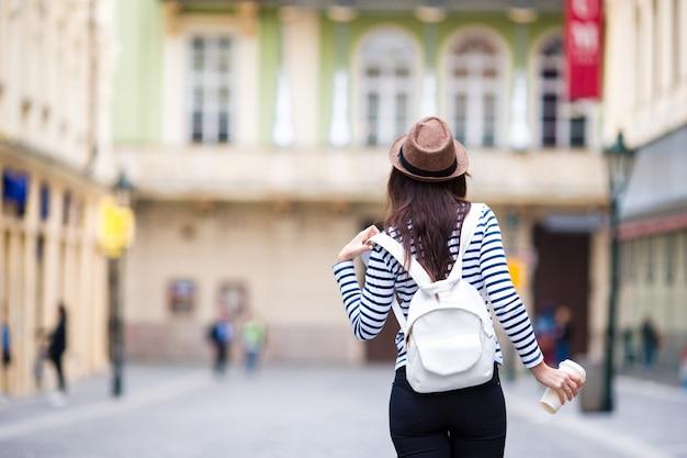 Gelukkige jonge stedelijke vrouw het drinken koffie in europese stad. de vrouw van de reistoerist met hete drank in praag in openlucht tijdens vakantie in europa.