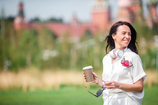 Gelukkige jonge stedelijke vrouw het drinken koffie in europese stad.