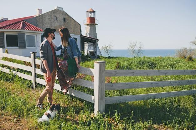 Gelukkige jonge stijlvolle hipster paar verliefd wandelen met hond in platteland, zomer stijl boho mode