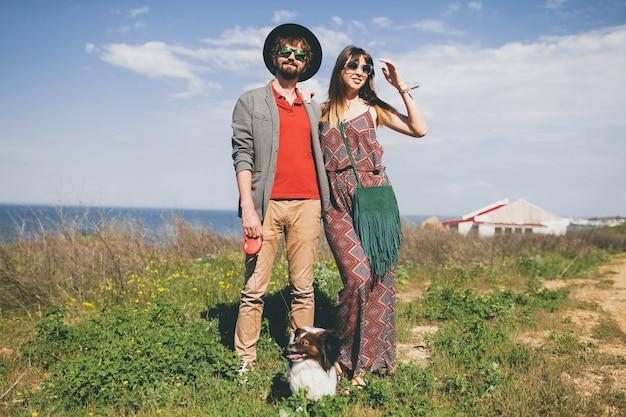 Gelukkige jonge stijlvolle hipster paar verliefd wandelen met hond in platteland