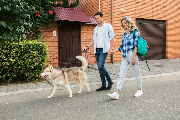 Gelukkige jonge stijlvolle paar wandelen met de hond in de straat