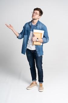 Gelukkige jonge student die zich volledige lengte met geïsoleerde boeken en nota's bevindt.