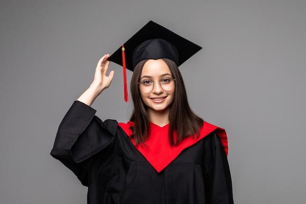 Gelukkige jonge student met diploma op grijs