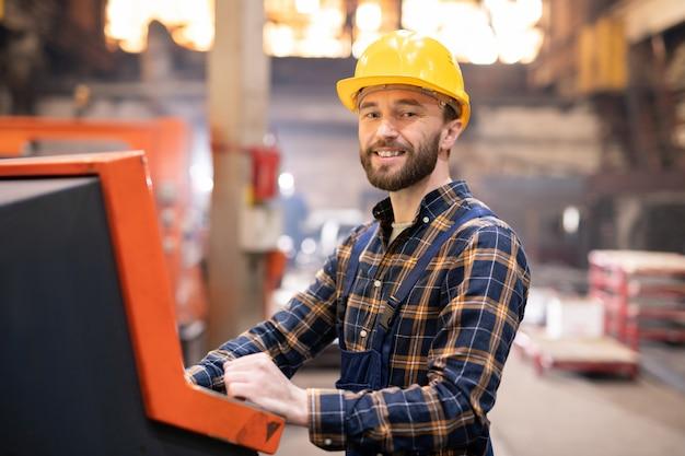 Gelukkige jonge succesvolle fabrieksingenieur in beschermende helm die u bekijkt terwijl het werkproces controleert