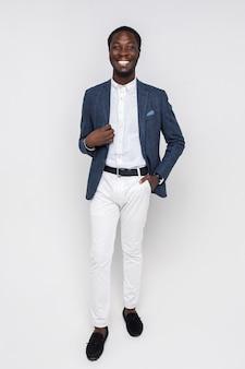 Gelukkige jonge succesvolle man in stijlvolle zakelijke kleding die op een geïsoleerde witte muur staat