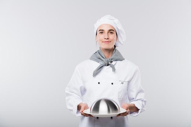 Gelukkige jonge succesvolle vrouwelijke chef-kok in eenvormige dragende glazen kap met gekookte maaltijd voor cliënt van restaurant