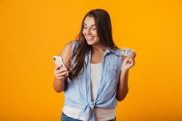 Gelukkige jonge te zware vrouw, die mobiele telefoon houdt, die plastic creditcard toont