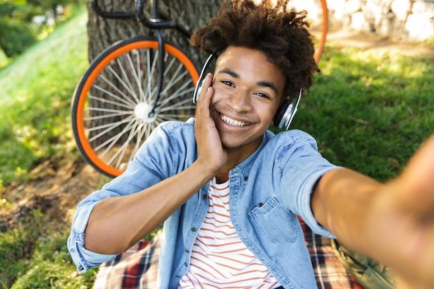 Gelukkige jonge tiener met fiets in openlucht