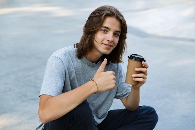 Gelukkige jonge tienerjongen die tijd doorbrengt in het skatepark, zittend op een skateboard, afhaalmaaltijden koffie te houden, duimen opgevend