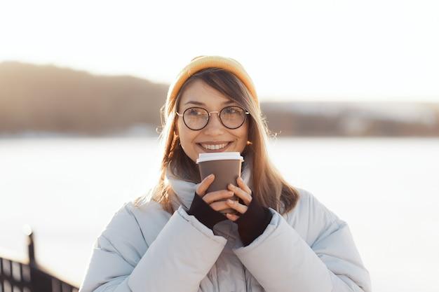 Gelukkige jonge tienervrouw die een meeneemkoffiekop houdt