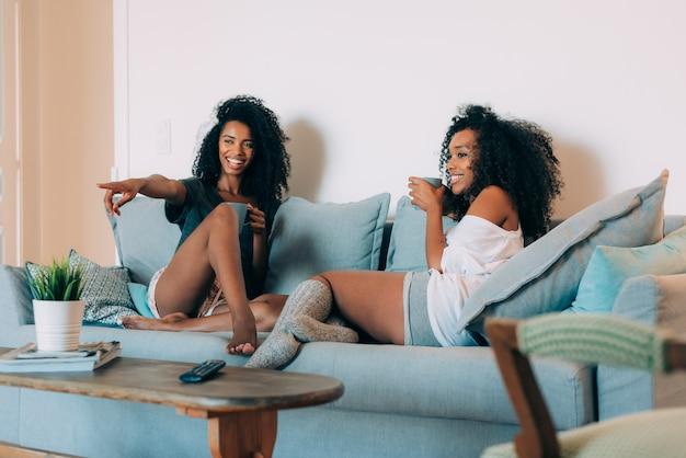 Gelukkige jonge twee zwarte vrouwen die in de laag het drinken koffie zitten