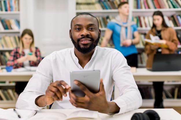 Gelukkige jonge universitaire multiraciale studenten die met boeken in bibliotheek bestuderen. knappe afrikaanse man kijken camera zittend aan tafel
