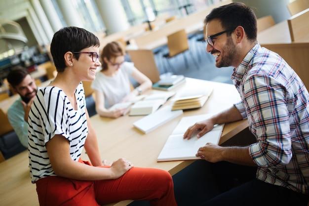 Gelukkige jonge universiteitsstudenten studeren met boeken in de bibliotheek. groep multiraciale mensen in universiteitsbibliotheek.